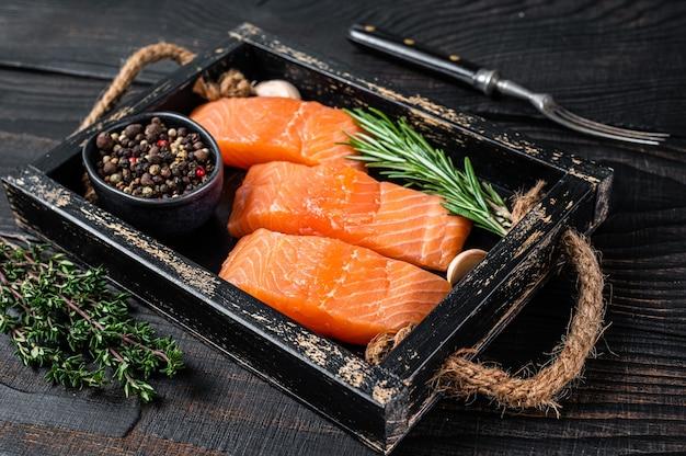 Filetto di salmone crudo bistecche di pesce in un vassoio di legno con timo e rosmarino. fondo in legno nero. vista dall'alto.