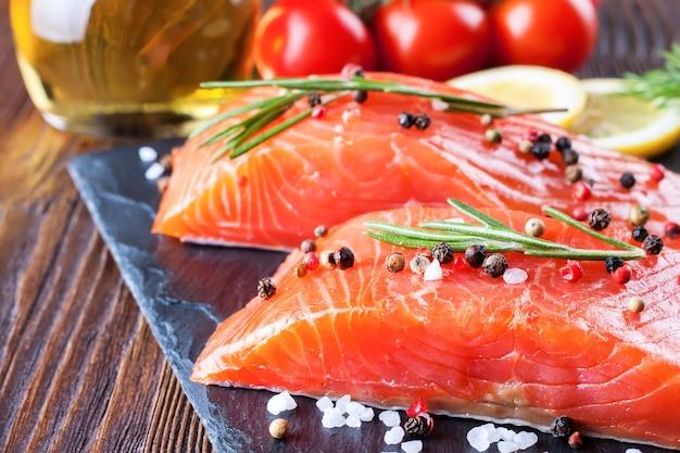 Filetto di salmone crudo e ingredienti per la cottura su una tavola di slade e fondo di legno marrone.