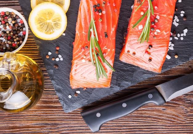 Filetto di salmone crudo e ingredienti per cucinare su un tagliere e un coltello su fondo di legno marrone.