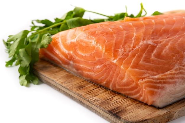 Filetto di salmone crudo e prezzemolo sul tagliere isolato su priorità bassa bianca