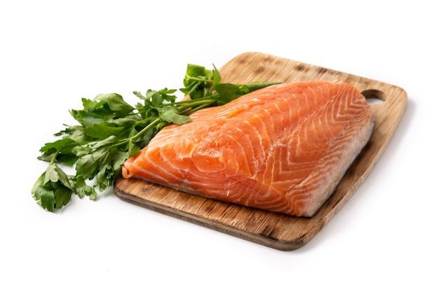 Filetto di color salmone crudo e prezzemolo sul tagliere isolato