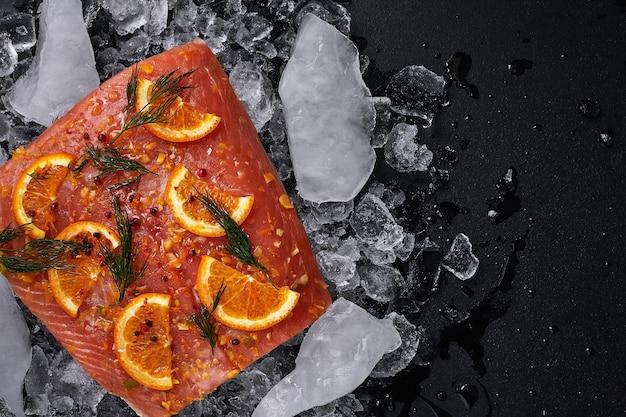 Filetto di salmone crudo con fette d'arancia su pezzi di ghiaccio su sfondo nero