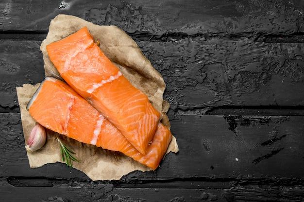 Filetto di pesce salmone crudo con spezie su tavola rustica nera.