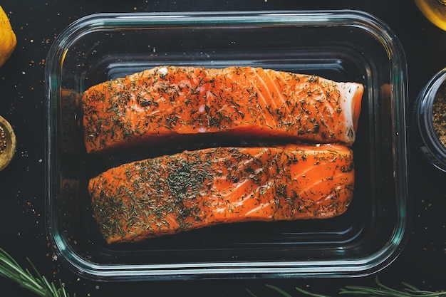 Pezzi di salmone crudo con spezie e aneto sulla scatola del pranzo