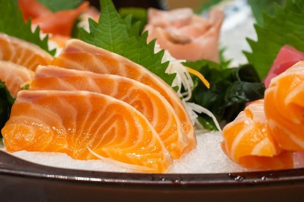 Fetta di sashimi di salmone crudo su ghiaccio cibo giapponese