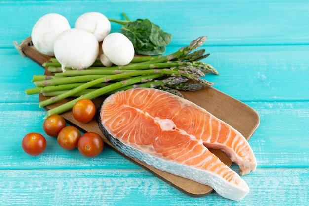 Fetta di salmone crudo con decorazione vegetale su sfondo blu. copia spazio.