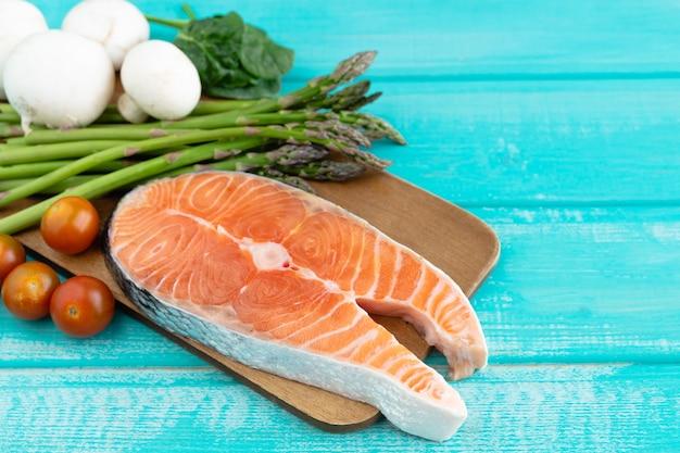 Fetta di salmone crudo con decorazione vegetale su superficie blu. copia spazio.