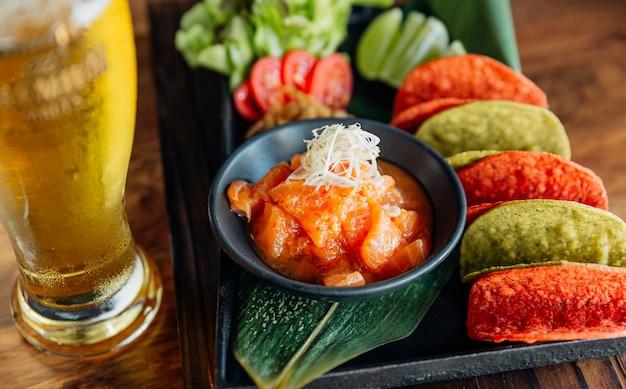 Insalata piccante di salmone crudo servita con patatine croccanti rosse e verdi per canape e birra fredda.