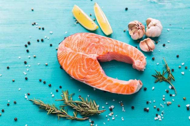 Trancio di salmone crudo su sfondo blu, vista dall'alto. cibo sano, dieta e concetto di cucina mediterranea