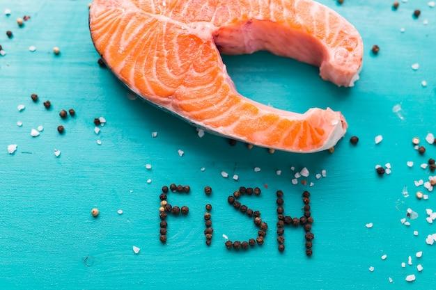 Bistecca di color salmone crudo su superficie blu e la scritta pepe pesce, vista dall'alto. cibo sano, dieta