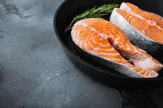 Trancio di salmone crudo in padella alla griglia, su sfondo grigio con spazio per il testo.