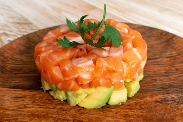 Tartare di salmone crudo, tartare di trota o cubetti di pesce rosso insalata con primo piano di avocado fresco. deliziosa bistecca di tonno crudo tartaro o sashimi sulla piastra del ristorante rustico in legno