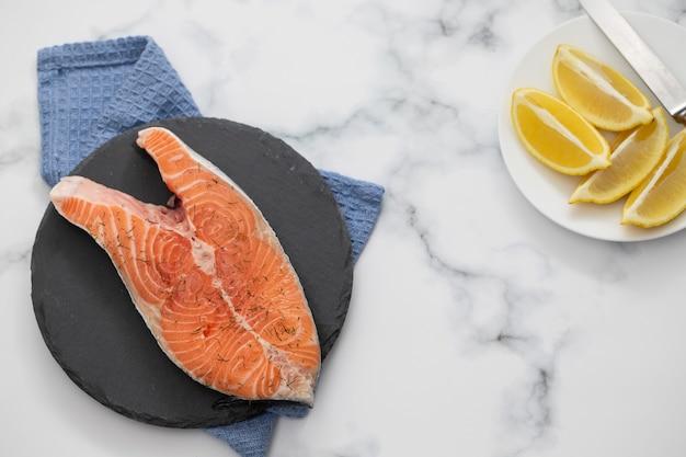 Salmone crudo con limone su tavola di ceramica nera