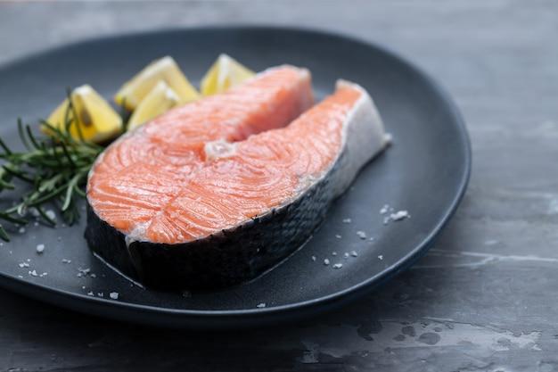 Salmone crudo con rosmarino e limone sul piatto scuro