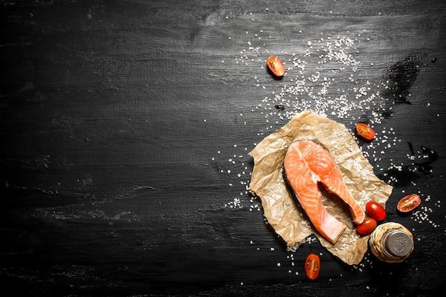 Salmone crudo con pomodori e sale sulla lavagna nera.