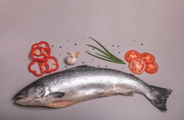 Salmone crudo con verdure e spezie su uno sfondo grigio