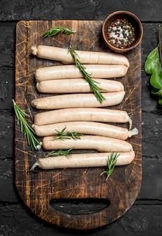 Salsicce crude con condimenti ed erbe aromatiche. sulla tavola rustica nera.