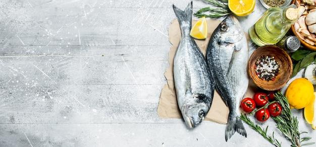 Dorado di pesce di mare crudo con limone e spezie aromatiche. su fondo rustico.