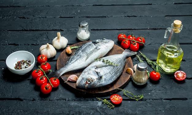 Dorado di pesce di mare crudo con condimenti e pomodori. su uno sfondo nero rustico.