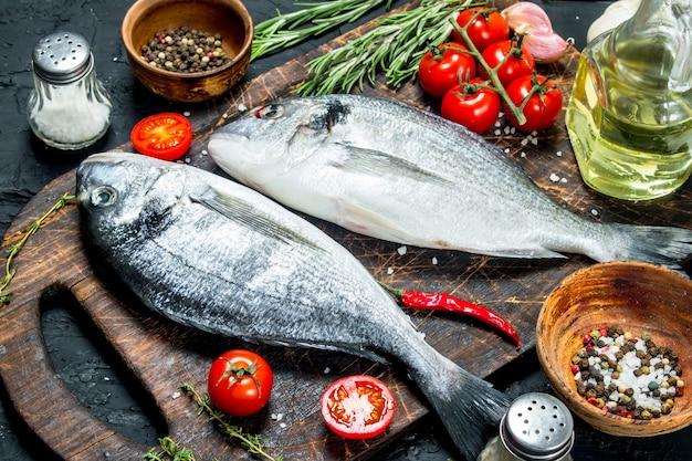 Dorado di pesce di mare crudo con spezie e rosmarino. su uno sfondo nero rustico.