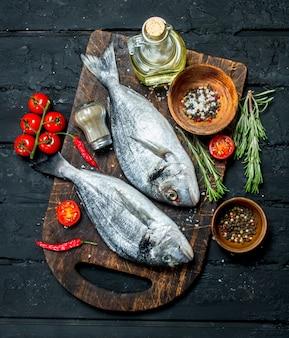 Dorado di pesce di mare crudo con spezie e rosmarino su un tavolo rustico nero.