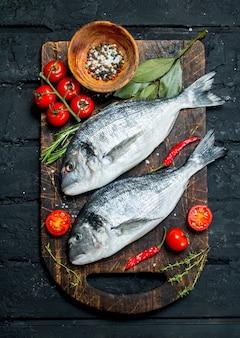 Dorado di pesce di mare crudo con pomodori, erbe e spezie. su un rustico nero.