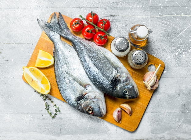 Dorado di pesce di mare crudo con pomodori, spicchi di limone e spezie. su un rustico.