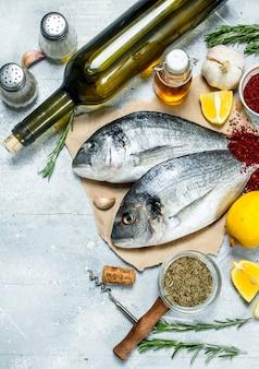 Dorado di pesce di mare crudo con vino bianco e spezie. su fondo rustico.