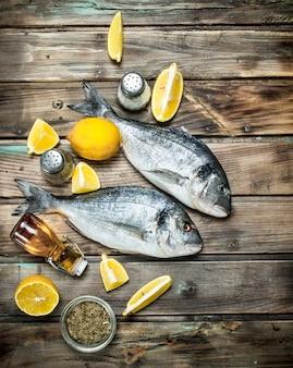 Pesce di mare crudo con fettine di limone e spezie aromatiche. su uno sfondo di legno.