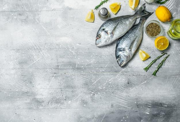 Pesce di mare crudo con spicchi di limone e aglio. su fondo rustico.