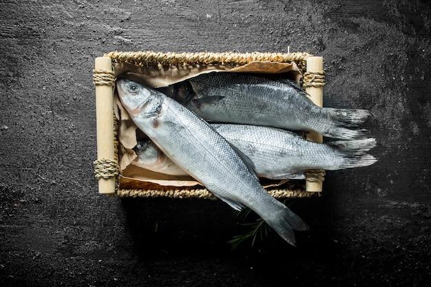 Spigola cruda di pesce nel cestello. sul nero rustico