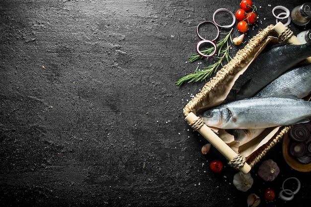 Pesce branzino crudo in un cesto con rosmarino, aglio e pomodorini su tavola rustica nera.