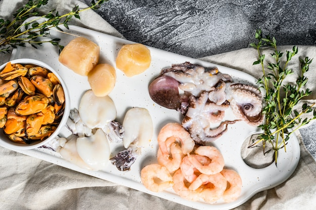 Mix di frutti di mare crudi su un tagliere di ceramica. muro grigio. vista dall'alto.