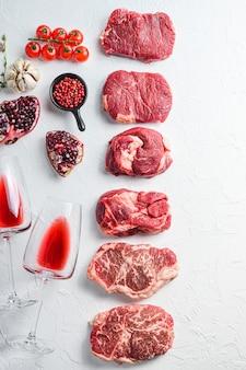 Set crudo di tagli di manzo alternativi chuck eye roll, lama superiore, bistecca di fesa con vino rosso in vetro e bottiglia, erbe e melograno. carne biologica. sfondo bianco con texture vista dall'alto con spazio per il testo.