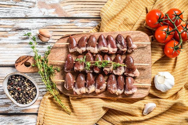 Spiedino di shish crudo con cuori di pollo su uno spiedino di legno. sfondo bianco. vista dall'alto.