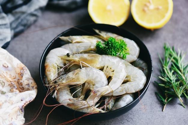 Gamberi crudi in ciotola, frutti di mare freschi di gamberetti con erbe e spezie per cibi cotti