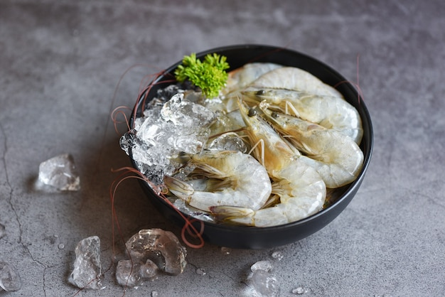 Gamberi crudi su ghiaccio in una ciotola, frutti di mare freschi di gamberetti con erbe e spezie