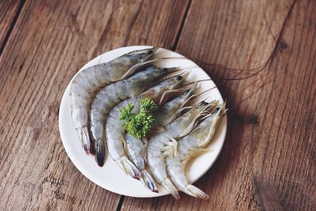 Gamberetti crudi su piatto bianco, frutti di mare freschi di gamberetti per cibo cotto - vista dall'alto