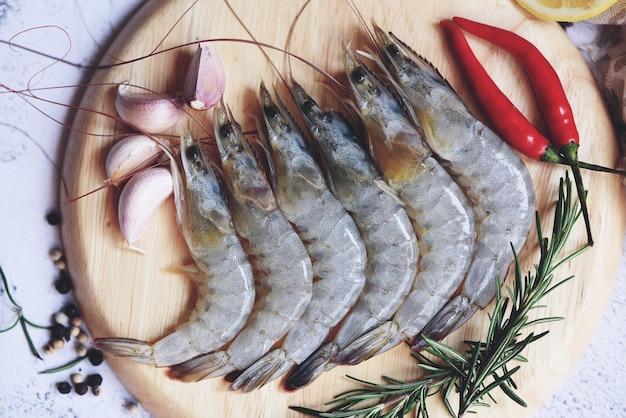 Gamberi crudi su piatto bianco, frutti di mare freschi di gamberetti con erbe e spezie per cibi cotti