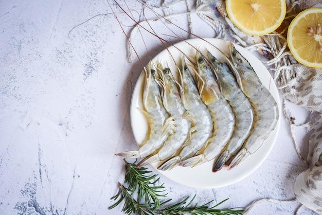 Gamberi crudi su piatto bianco, frutti di mare freschi di gamberetti con erbe e spezie - vista dall'alto