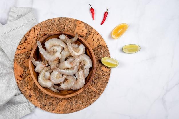 Gamberi crudi o gamberi in piatto di legno con calce e peperoncino rosso pronto per la cottura.