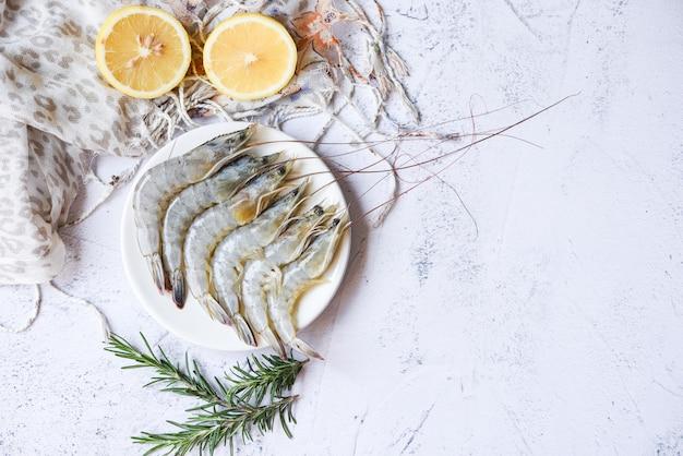 Gamberetti crudi sulla zolla bianca con erbe e limone