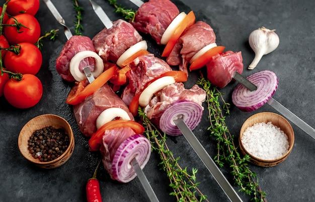 Spiedini di carne crudi. carne barbecue con verdure e spezie.