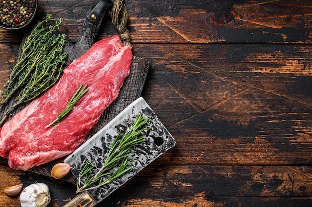 Bistecca di carne di manzo machete gonna cruda su un tagliere con mannaia. fondo in legno scuro. vista dall'alto. copia spazio.