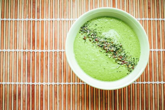 Zuppa cruda con avocado, piselli, spinaci e spezie per una dieta sana, servizio di consegna di cibo e concetto di ordine online