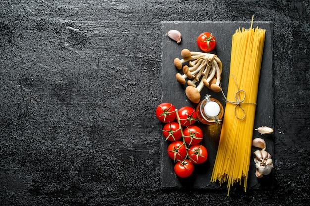 Spaghetti crudi sul bordo di pietra nera con pomodori, aglio, funghi e olio. sul nero rustico