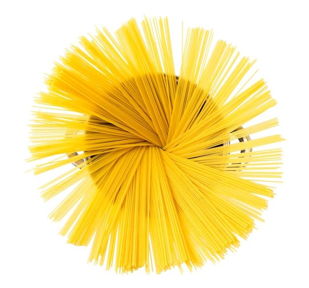 Gli spaghetti crudi vengono versati in una padella di metallo su uno sfondo bianco. la vista dall'alto