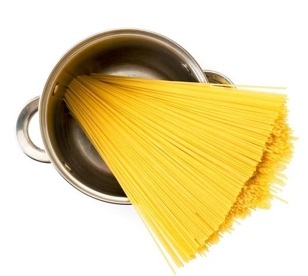 Spaghetti crudi in una padella di metallo su uno sfondo bianco. la vista dall'alto