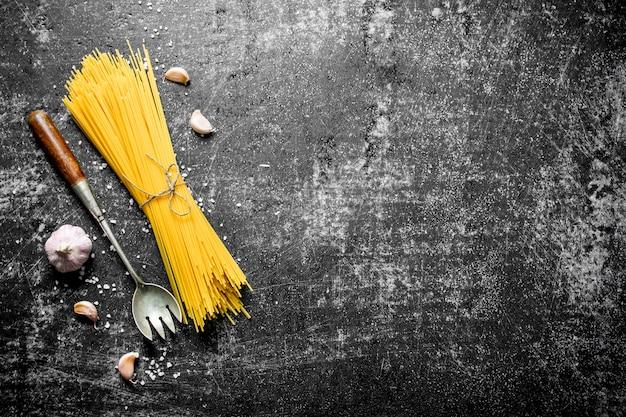 Spaghetti crudi con aglio e un mestolo. su sfondo nero rustico