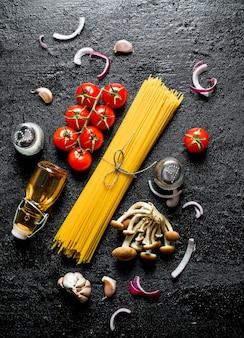 Spaghetti crudi con fette di cipolla, pomodori, funghi e olio in una bottiglia. su sfondo nero rustico